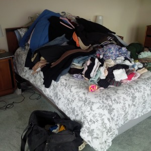 Clothes in pile on bed, before tidying